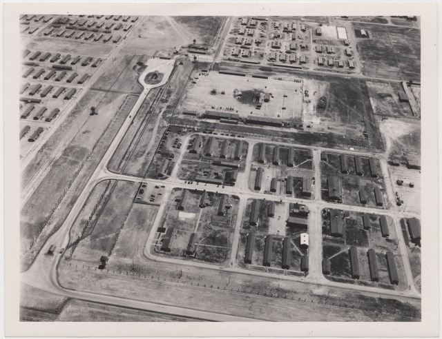Tule Lake Center, 6 July 1945. Aerial view showing Military Police Area, left foreground, and WRA Adminstration Area in center and right background. Part of the evacuee area is shown beyond the fire break.