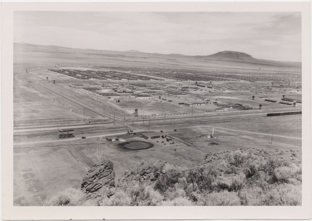 Tule Lake Center, 6 July 1945. Panoramic view from the Butte west of the Center. Military Police stable area in foreground. Military Police area (center); WRA Area (right center); evacuee area (background). Note highway and railroad.