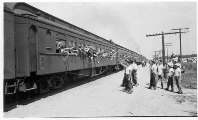 A carful of Hawaiian evacuees waving farewell as their segregation train left Jerome for the Tule Lake Center. -- Photographer: Lynn, Charles R. -- Dermott, Arkansas. 9/19/43. Source.