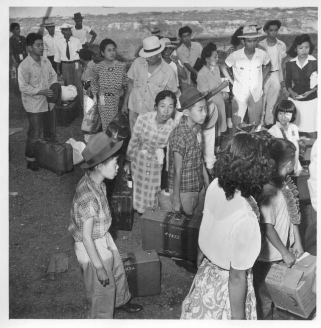 Closing of the Jerome Center, Denson, Arkansas. Jerome residents with their hand luggage wait at the [illegible] car entrance for their names to be called by the W.R.A. official checking the list. -- Photographer: Iwasaki, Hikaru -- Denson, Arkansas. 6/18/44. Source.