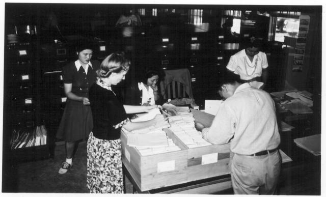 Left to right are Masako Mikami, Miss Gladys Townsend, Chiyoka Kawanami, George Nakaji, Aiko Nishikata of the Jerome Office Services Section assembling the files for persons being transferred to Tule Lake. -- Photographer: Lynn, Charles R. -- Dermott, Arkansas. 9/19/43. Source.