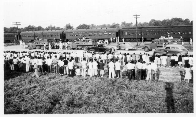 Four trucks (three can be seen in this picture) were used to transport segregees from their blocks to each car on the first segregation train (trip 4) to leave this center for Tule Lake. Large crowd of center residents (foreground) came to watch the train off but stayed inside the boundary fence on this side of the road. With the segregees came their hand luggage. -- Photographer: Lynn, Charles R. -- Dermott, Arkansas. 9/15/43. Source.