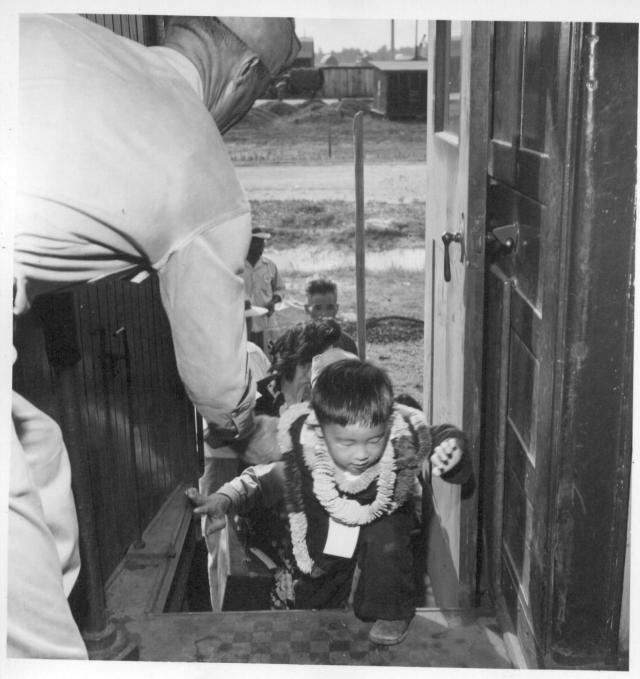 Closing of the Jerome Center, Denson, Arkansas. Travel is just another adventure to the children of the relocation centers. Here a little tot eagerly mounts the steps of the chair car assisted by a member of the military police. -- Photographer: Iwasaki, Hikaru -- Denson, Arkansas. 6/15/44. Source.