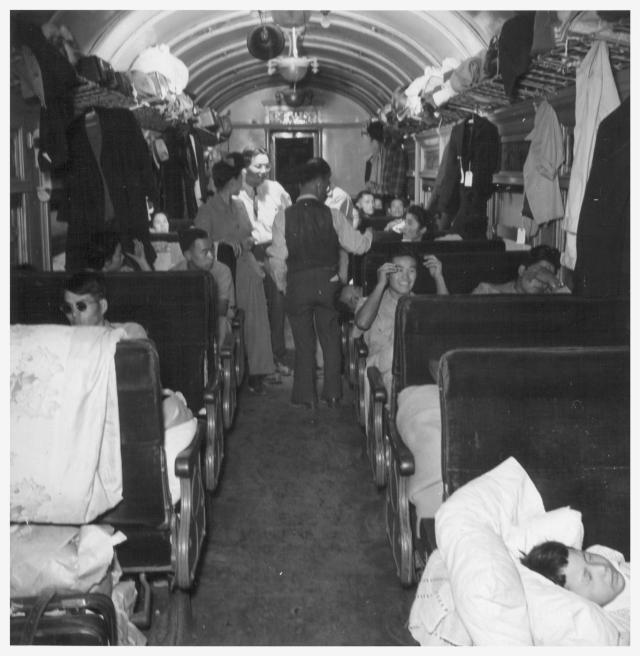 A scene in one of the twenty coaches on trip 15, Topaz to Tule Lake. The train monitor is seen conferring with a car captain and some of the passengers regarding the comfort of the latter. Photographer: Mace, Charles E. , 9/24/43