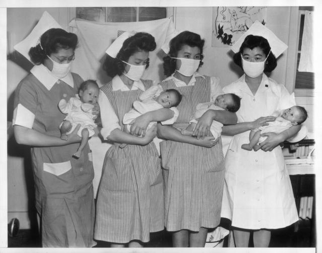 Stork Visits Relocation Center -- The stork has paid frequent visits to the Tule Lake, California, Japanese relocation center since it was opened a year ago. Here are four new arrivals held by nurses (L-R) Mary Nitta, Loomis, California; Ruby Fujioki, Seattle, Wash.; Masako Nakadoi, Loomis, California, Katsumi Ogawa, Loomis, California JARDA-6-11 1943-05-21