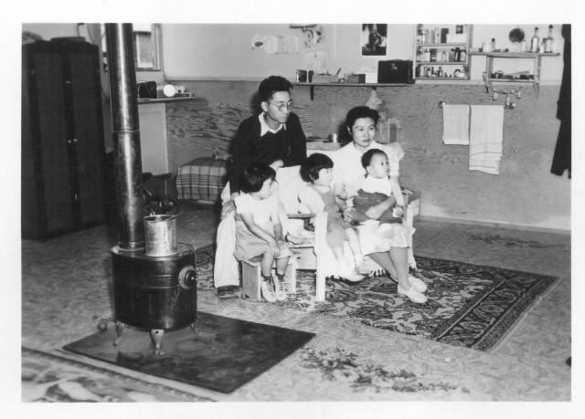 An evacuee family spends a quiet evening in their barracks. The decoration of this apartment is quite typical and shows the home made furniture, shelves, bookcases and other furniture. -- Photographer: Stewart, Francis -- Newell, California. 9/10/42. Source.