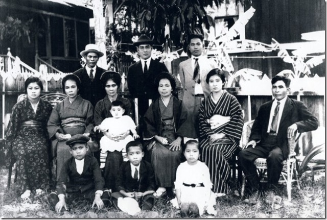 photograph of the Inafuku and Arashiro families with Mrs Wakukawa (sitting 2nd from left, Seiyei Wakukawa's mother) was taken I believe in Honolulu in 1921 before my grandmother (4th from left), my Dad Ronald (middle sitting on ground), and my aunty Annie (young girl sitting on ground) left Hawaii to bring the remains of my grandfather Hoyei Inafuku back to Haneji Okinawa.  Grandfather Hoyei passed away from influenza in Waimea Kauai in Aug 1918. Hoichi Inafuku with the white hat is standing on the left and his younger brother Raymond Hotoku Inafuku is standing on the right.  The others in the photograph are members of the Arashiro family.  Anso Arashiro who is sitting on the right is my grandmother Kamado Arashiro Inafuku's brother.