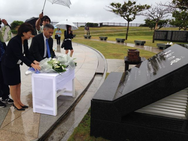 Laying fresh flowers at the Cornerstone of Peace, a monument which commemorates the Battle of Okinawa and the end of World War II. — in Itoman, Okinawa.